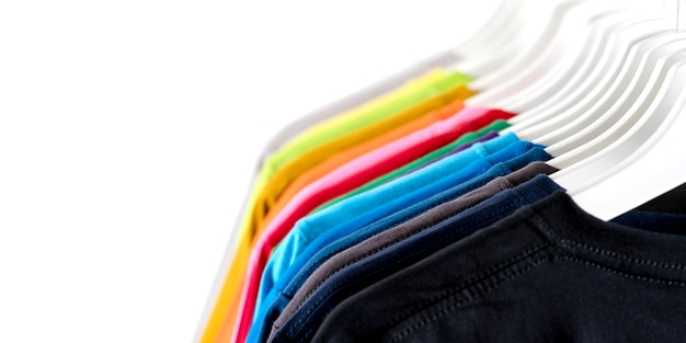 Close-up de camisetas, roupas em cabides no fundo branco
