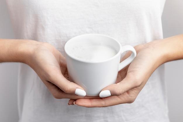 Close-up de caneca com leite realizada nas mãos