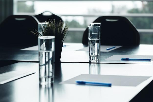 Close-up de canetas de óculos de água de mesa de conferência escura, folhas de papel