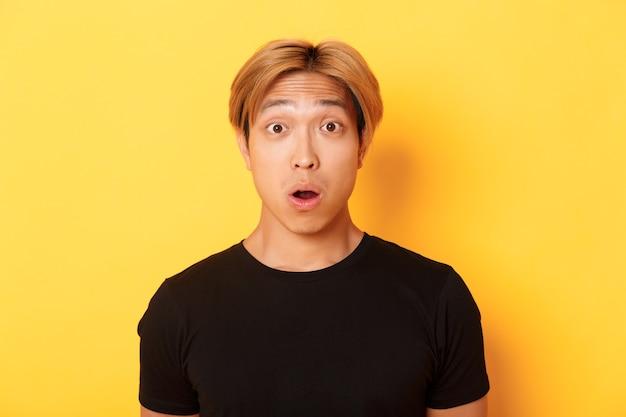 Close-up de cara asiático surpreso e sem palavras, mandíbula de cair e levantando as sobrancelhas espantado, em pé sobre a parede amarela.