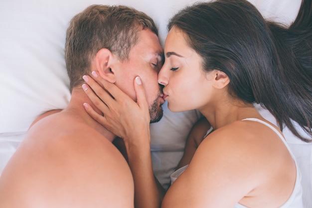 Close-up de cara e mulher deitada na cama e beijar
