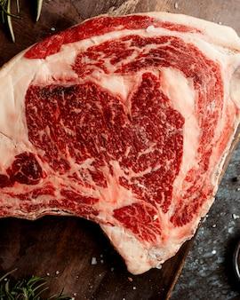 Close-up de carne de cordeiro crua, colocada na placa de madeira