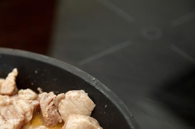 Close-up de carne de pedaços fritos, carne de porco cozida de carne gorda com creme de leite em casa. alimentos cozidos na frigideira. muita gordura. deliciosa fritura de produtos de carne. cozinhar guisado em estilo rústico, vista de cima