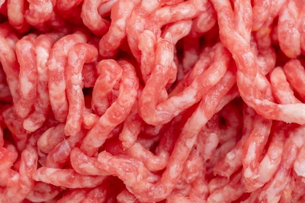 Close-up de carne de porco e boi picada enrolada em um moedor de carne, carne picada para cozinhar. conceito de comida saudável, comida natural.