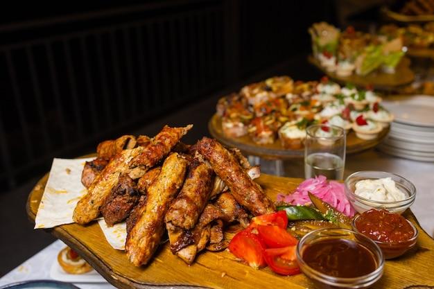 Close-up de carne variada em um prato. diferentes tipos de carne e batatas em uma pilha. aperitivo em um prato grande com molhos.