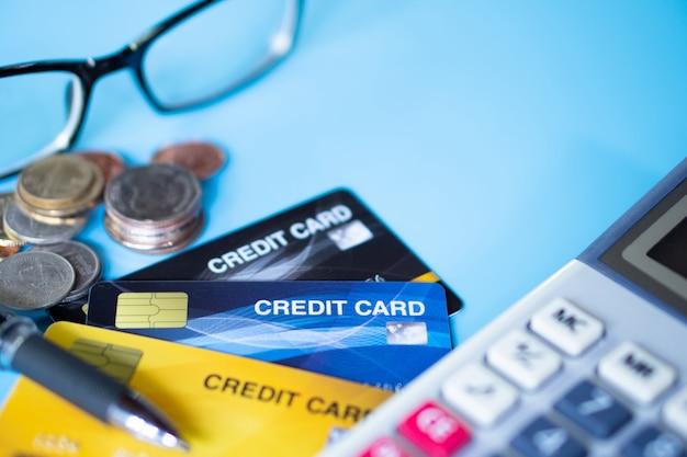Close-up de cartão de crédito colorido com moeda e calculadora