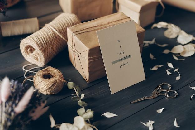 Close-up de cartão para pessoa especial apoiado em um presente embalado, tesouras, fios, pétalas na mesa de madeira