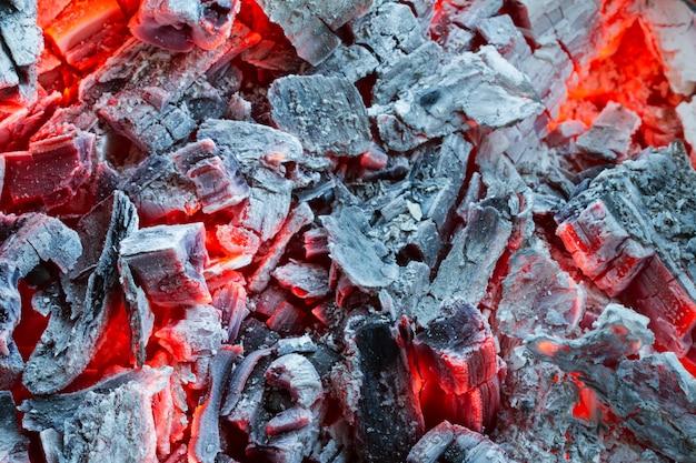 Close up de carvões smouldering, carvão ardente na obscuridade. cinzas no churrasco.