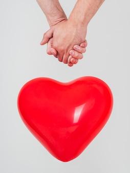 Close-up de casal gay de mãos dadas com balão