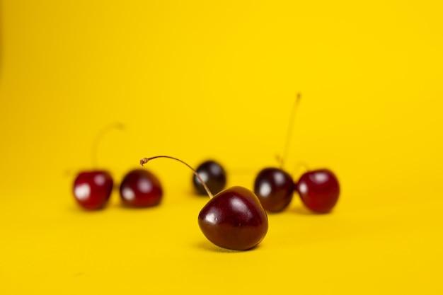 Close-up de cerejas maduras em um fundo amarelo.