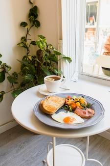 Close-up de chá de ervas; ovos recém cozidos; salada; bacon e torradas no prato por cima da mesa
