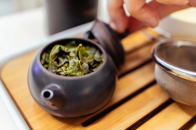 Close-up de chá verde chinês com água quente dentro da chaleira pequena de cerâmica em um copo pequeno para fazer chá verde.