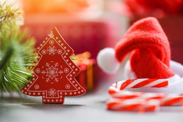 Close-up de chapéu de papai noel de natal e decorações caixa de presente de árvore de pinho de cana
