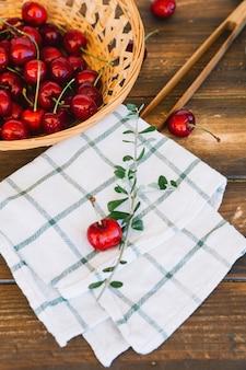Close-up, de, checkered padrão, guardanapo, e, cerejas vermelhas, em, tigela vime