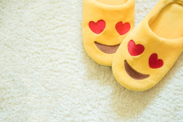 Close-up de chinelos de pelúcia amarelos feitos como o emoji sorridente com olhos de coração no tapete branco