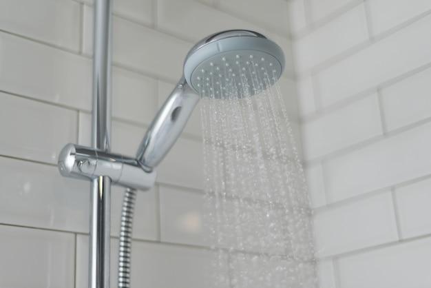 Close-up de chuveiro cromado, torneira, no banheiro