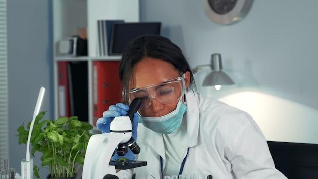 Close-up de cientista negra se surpreendendo com o resultado do experimento visto ao microscópio