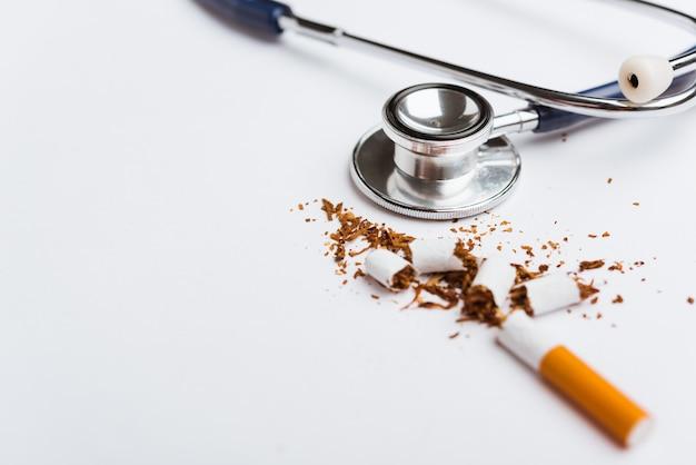 Close-up de cigarro quebrado pilha ou tabaco e estetoscópio médico