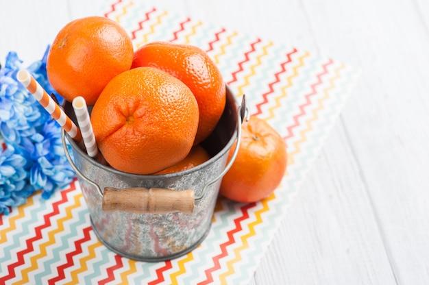 Close-up de clementinas frescas em um balde de lata