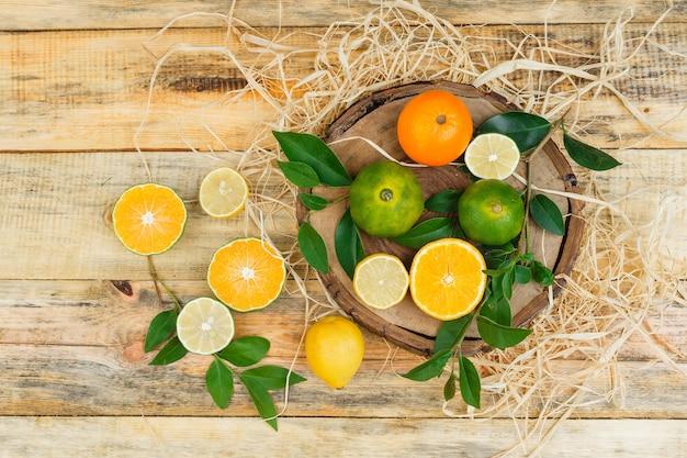Close-up de clementinas na placa de madeira com limão e tangerinas na placa de madeira