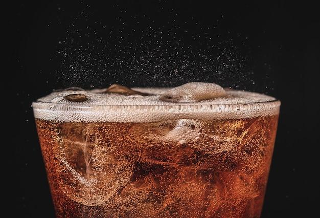Close-up de cola de gelo em vidro e refrigerante de bolha espirrando em fundo preto