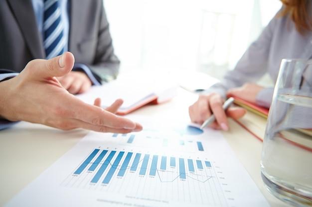 Close-up de colegas de trabalho que revêem as estatísticas