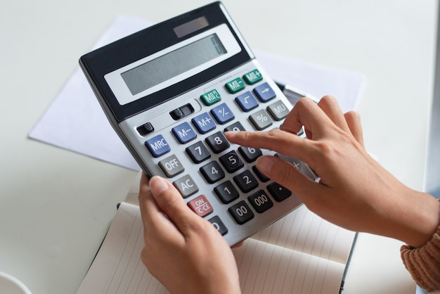 Close-up, de, contador, usando, calculadora, enquanto, examinando, relatório
