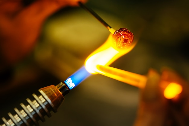 Close-up de contas de vidro derretendo no fogo do queimador de gás