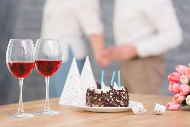 Close-up de copo de vinho; bolo delicioso; chifre de festa e tulipa flores na mesa de madeira