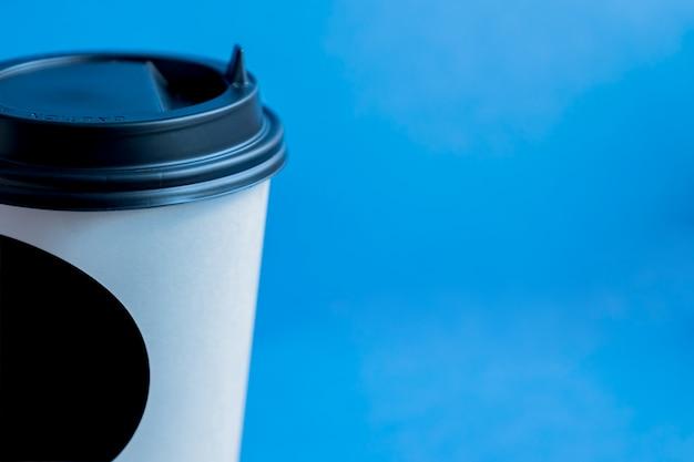 Close-up de copo descartável de papel branco kraft para café com tampa plástica preta em azul com espaço de cópia