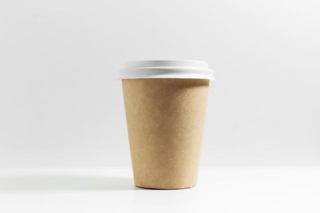 Close-up de copo descartável de papel para levar para café, com tampa branca, isolado no branco.