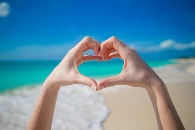 Close up de coração feito por mãos femininas na praia