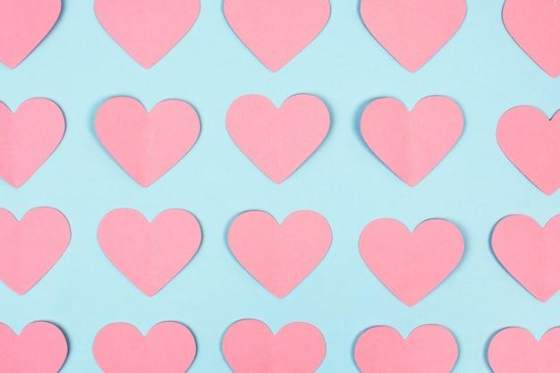 Close-up de corações de papel rosa sobre fundo azul. fundo sem emenda de corações de papel rosa. postura plana. vista do topo