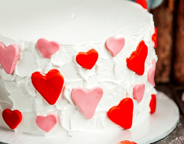 Close-up de corações fondant em vermelho e rosa no bolo cremoso branco