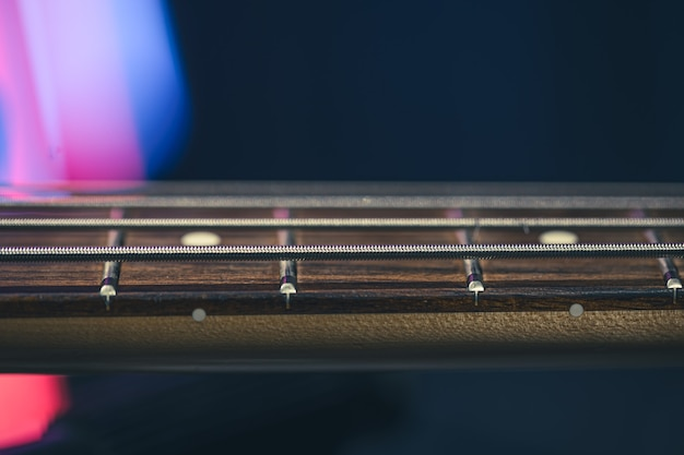 Close-up de cordas no braço da guitarra de um baixo em um fundo escuro turva.
