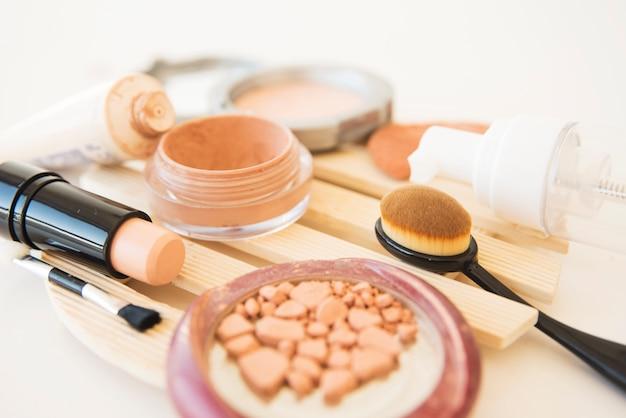 Close-up de cosméticos de uma mulher usou pó de maquiagem; escova; batom e creme