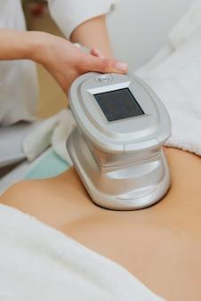 Close-up de cosmetologista fazendo massagem com aparato especial na barriga feminina.