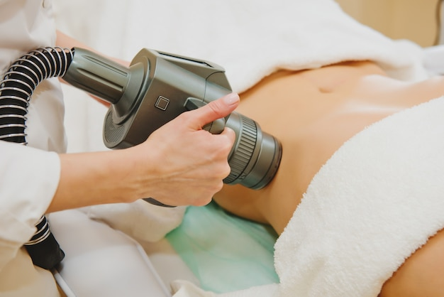 Close-up de cosmetologista fazendo massagem com aparelho de vácuo especial na barriga feminina.