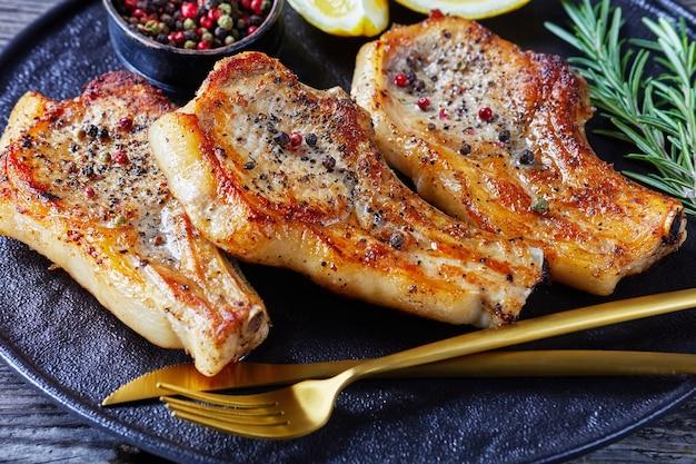 Close-up de costeletas de porco de costela fritas com rodelas de limão, alecrim, pimenta em grão e garfo dourado e faca em uma travessa preta