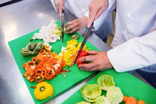 Close-up de cozinheiros chefe cortar legumes