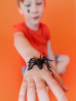 Close-up de criança segurando uma aranha de halloween