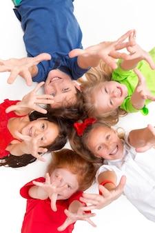 Close-up de crianças felizes, deitado no chão do estúdio e olhando para cima, isolado no fundo branco, vista superior. emoções para crianças e conceito de moda