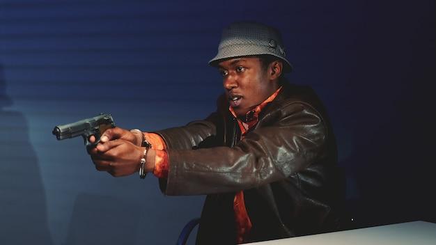 Close-up de criminoso preto pegando a arma e ameaçando prejudicar policiais