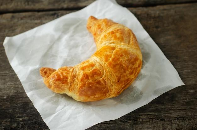 Close-up de croissant com papel branco na mesa de madeira