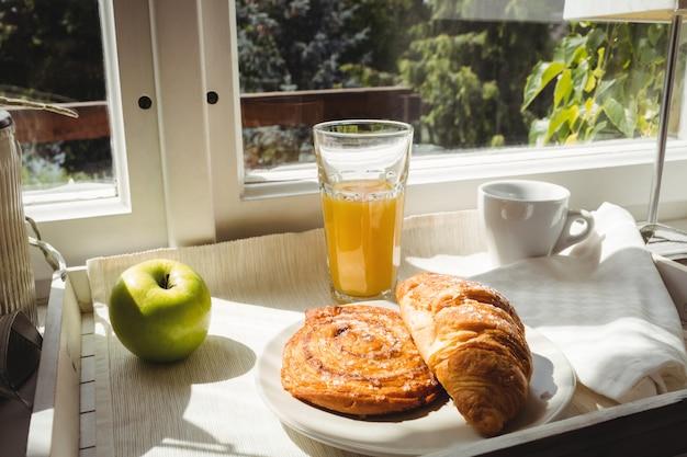 Close-up de croissant e copo de suco em uma bandeja