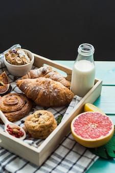 Close-up de croissant fresco; cookies com suporte; leite; muesli; e frutas cítricas com pano em recipiente de madeira
