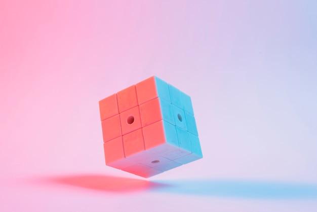 Close-up, de, cubo quebra-cabeça 3d, ligado, fundo cor-de-rosa
