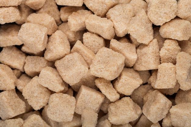 Close-up de cubos de açúcar não refinado marrom natural em branco. vista do topo