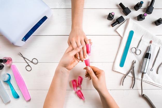 Close up de cuidado de unha de mãos femininas lixa de unhas com lixa de unha profissional no topo do salão de beleza ...