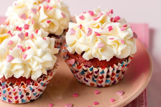 Close-up de cupcakes com granulado em forma de coração e glacê